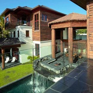 Foto di un ampio patio o portico etnico dietro casa con fontane, pavimentazioni in pietra naturale e un tetto a sbalzo