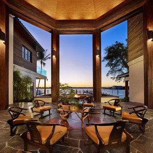 Esempio di un ampio patio o portico etnico in cortile con un focolare, pavimentazioni in pietra naturale e un gazebo o capanno