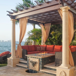 Photo of a small mediterranean back patio in Tampa with an outdoor kitchen and a pergola.