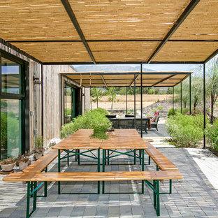 Imagen de patio de estilo de casa de campo con adoquines de hormigón y cenador