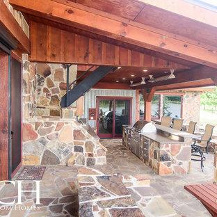 Foto di un ampio patio o portico rustico dietro casa con pavimentazioni in pietra naturale e un tetto a sbalzo