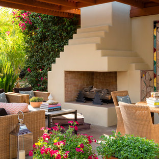 Inspiration for a patio in Los Angeles with a fire feature, natural stone paving and an awning.
