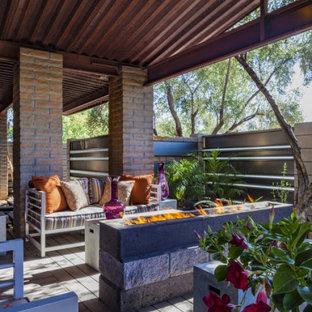 Ispirazione per un patio o portico industriale di medie dimensioni e in cortile con un focolare, pedane e un tetto a sbalzo