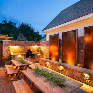 Example of a mid-sized mountain style backyard stone patio kitchen design in Denver with no cover