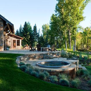Foto di un grande patio o portico rustico dietro casa con un focolare, pavimentazioni in pietra naturale e nessuna copertura