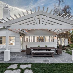 Foto di un patio o portico country di medie dimensioni e dietro casa con pavimentazioni in pietra naturale e una pergola