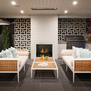 Inspiration for a mid-sized contemporary backyard tile patio remodel in Salt Lake City with a fireplace and a roof extension