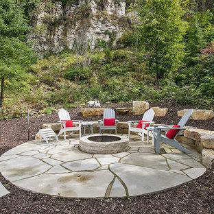 Exemple d'une petite terrasse arrière bord de mer avec des pavés en pierre naturelle, un foyer extérieur et aucune couverture.