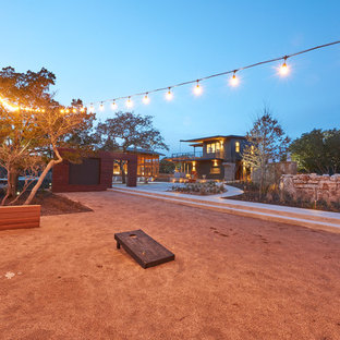 Medium sized modern back patio in Austin with concrete paving and an awning.