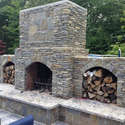 Open Air expansion - This amazing stone fireplace with granite hearth custom built by THE OUTDOOR KITCHEN DESIGN STORE by PREFERRED PROPERTIES is the central link between the Outdoor living space and the outdoor Kitchen. The more dramatic the Outdoor fireplace. The more dramatic the outdoor living space. The stone on this outdoor fireplace is both stacked stone and square and rectangular thin cut. Both full bed stone and thin cut stone with double thick Azul granite for the hearth. Top shelf in granite yet to be installed.