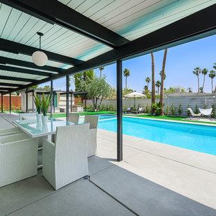 Foto di un patio o portico design con lastre di cemento e un tetto a sbalzo