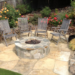 Mid-sized elegant backyard stone patio photo in San Francisco with a fire pit
