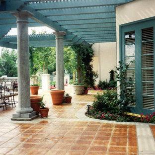 Ispirazione per un patio o portico mediterraneo di medie dimensioni e dietro casa con un caminetto, cemento stampato e un gazebo o capanno