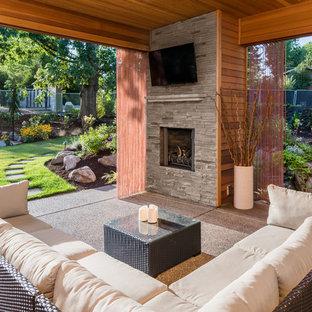 Ispirazione per un patio o portico classico di medie dimensioni e dietro casa con un focolare, graniglia di granito e un tetto a sbalzo