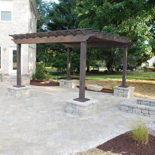 Inspiration for a large timeless backyard brick patio remodel in Other with a fire pit and a pergola