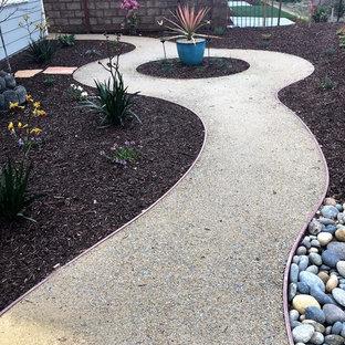 Foto di un grande patio o portico minimalista con un focolare e graniglia di granito