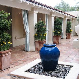 Foto di un grande patio o portico mediterraneo dietro casa con fontane, piastrelle e un tetto a sbalzo