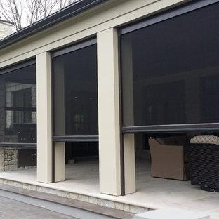 Réalisation d'une grande terrasse arrière tradition avec des pavés en béton et une extension de toiture.