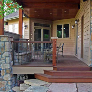 Example of a mid-sized mountain style backyard stone patio design in Denver with a roof extension