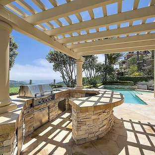 Photo of a medium sized mediterranean back patio in Los Angeles with an outdoor kitchen, no cover and natural stone paving.