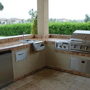 Example of a mid-sized trendy backyard stone patio kitchen design in Miami with a gazebo