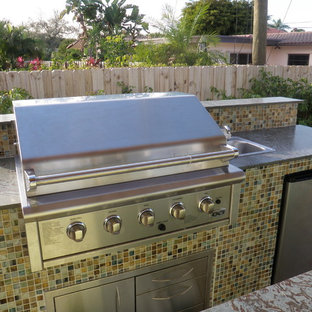 Example of a mid-sized trendy backyard stone patio kitchen design in Miami with no cover