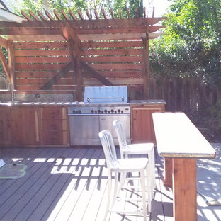 Example of a mid-sized cottage backyard patio design in San Francisco with decking and a pergola