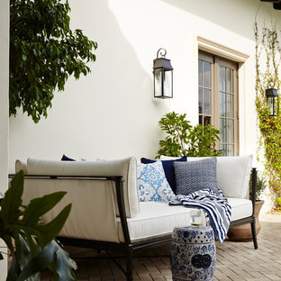 Expansive mediterranean courtyard patio in Miami with a water feature and brick pavers.