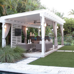 Design ideas for a medium sized contemporary back patio in Miami with an outdoor kitchen, natural stone paving and a gazebo.
