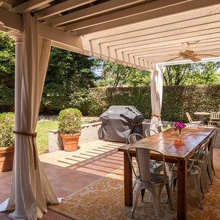 Foto di un patio o portico eclettico di medie dimensioni e dietro casa con piastrelle e una pergola