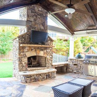 Idee per un grande patio o portico tradizionale dietro casa con un focolare e pavimentazioni in cemento