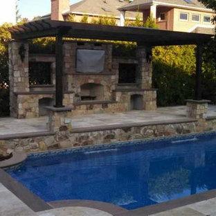 Immagine di un grande patio o portico mediterraneo dietro casa con un focolare, pavimentazioni in pietra naturale e una pergola