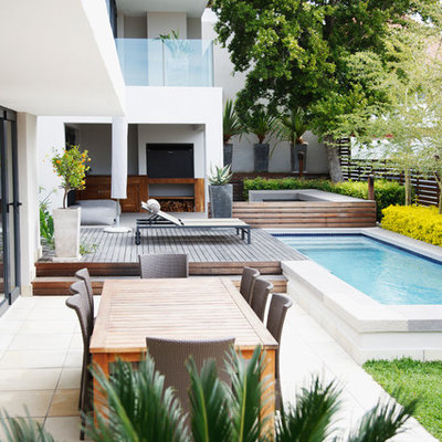 Example of a trendy side yard patio design in Houston with decking and no cover