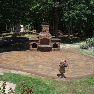 Foto di un grande patio o portico country dietro casa con un focolare, pavimentazioni in mattoni e nessuna copertura