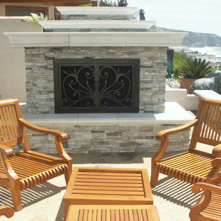 Mid-sized elegant backyard stone patio photo in San Diego with a fire pit