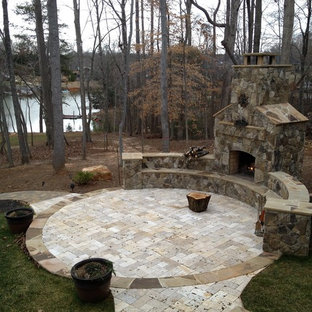 Inspiration for a large craftsman courtyard stone patio remodel in Charlotte with a fire pit and no cover