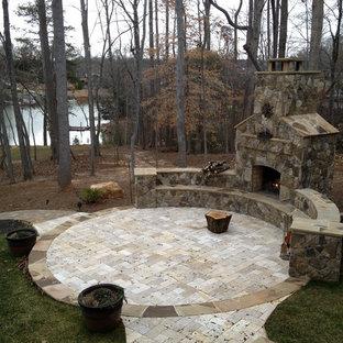 Idee per un grande patio o portico american style in cortile con un focolare, pavimentazioni in pietra naturale e nessuna copertura