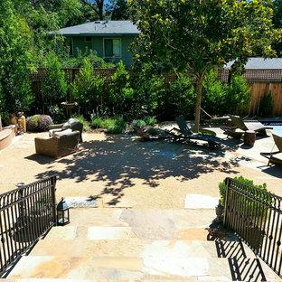 Foto di un patio o portico design di medie dimensioni e in cortile con un focolare e graniglia di granito