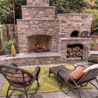 Immagine di un patio o portico chic con un focolare