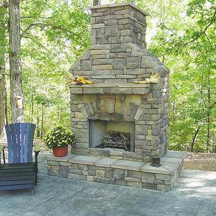 Esempio di un grande patio o portico chic dietro casa con un caminetto, cemento stampato e nessuna copertura