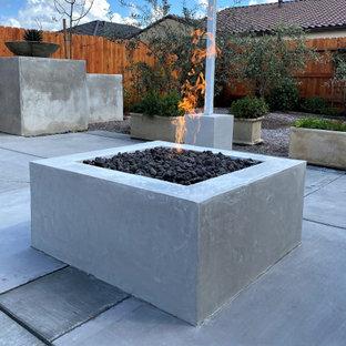 Immagine di un patio o portico american style di medie dimensioni e dietro casa con un caminetto, lastre di cemento e un gazebo o capanno