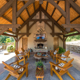 Patio - large rustic backyard stone patio idea in Other with a roof extension and a fireplace