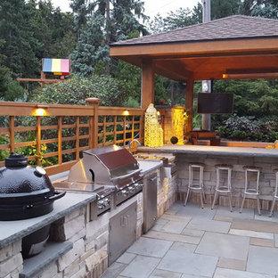 Idee per un grande patio o portico tradizionale dietro casa con pavimentazioni in pietra naturale e un gazebo o capanno