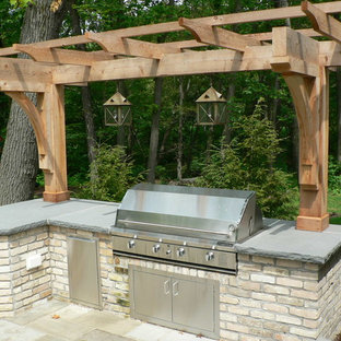 Example of a small classic backyard stone patio kitchen design in Milwaukee with a pergola