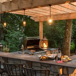 Patio kitchen - mid-sized traditional backyard stone patio kitchen idea in Minneapolis with a pergola