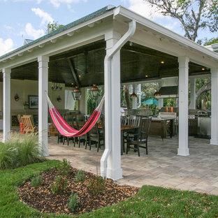 Cette photo montre une terrasse arrière bord de mer avec des pavés en béton et une extension de toiture.