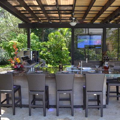 Huge elegant backyard stone patio kitchen photo in Miami with a pergola