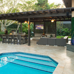 Photo of an expansive traditional back patio in Miami with an outdoor kitchen, natural stone paving and a pergola.