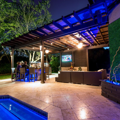 Inspiration for a huge timeless backyard stone patio kitchen remodel in Miami with a pergola