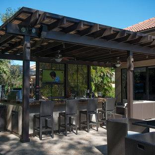 Modelo de patio tradicional, extra grande, en patio trasero, con cocina exterior, adoquines de piedra natural y pérgola